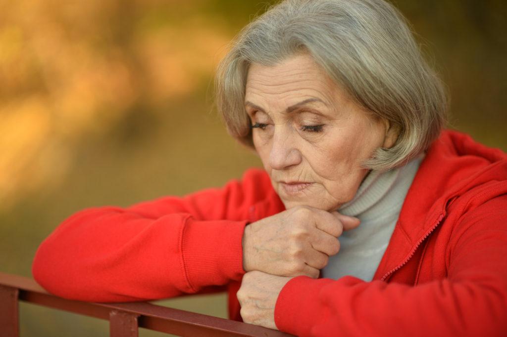 A thoughtful senior woman looks a little sad.