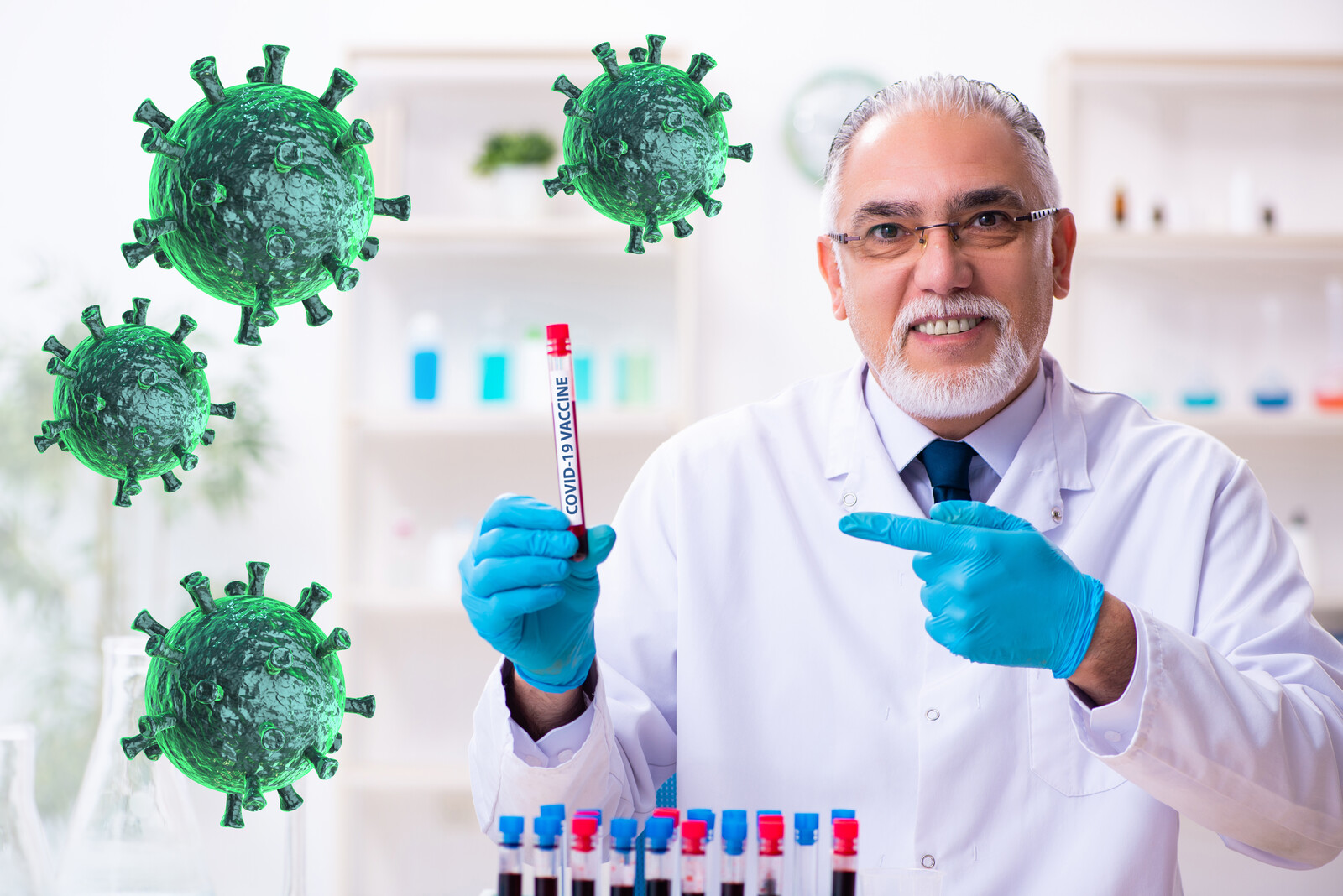 A senior doctor in a lab holding up a vile that says COVID-19 vaccine, on the left are green virus molecules floating over the photo