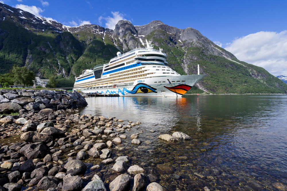 A Carnival cruise ship by a rocky shore and mountains in Norway