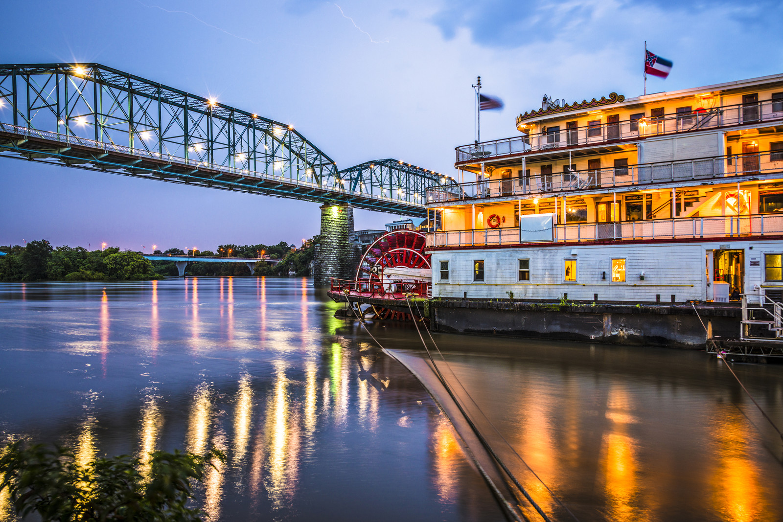 Chattanooga paddleboat on the river in the evening with the lights of the boat reflecting ff the water.  A bridge is on the left side if the photo