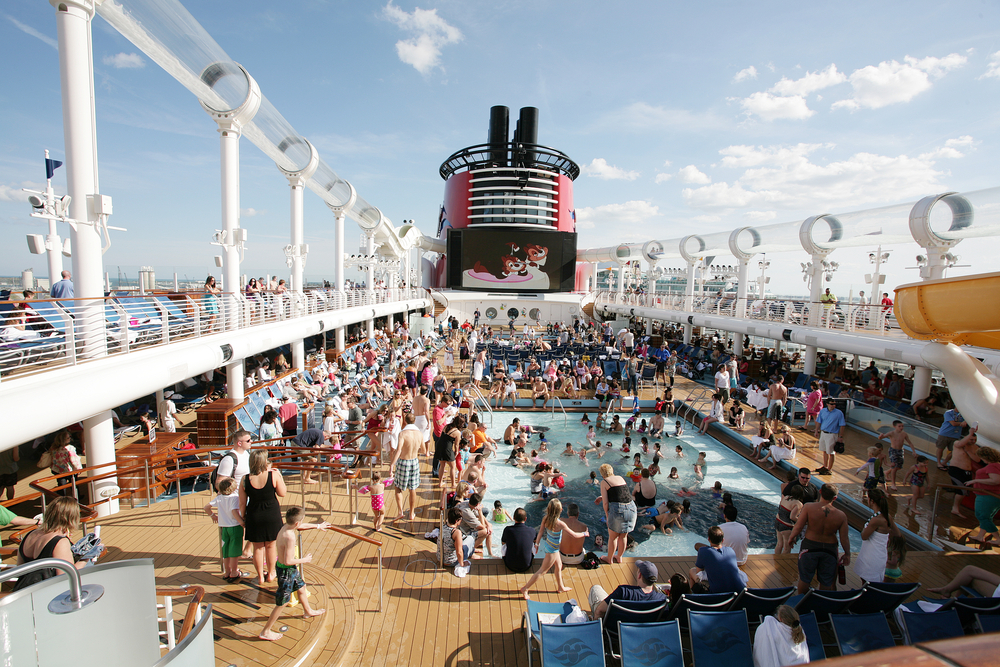 Deck of a Disney cruise ship packed full of people under a blue sky