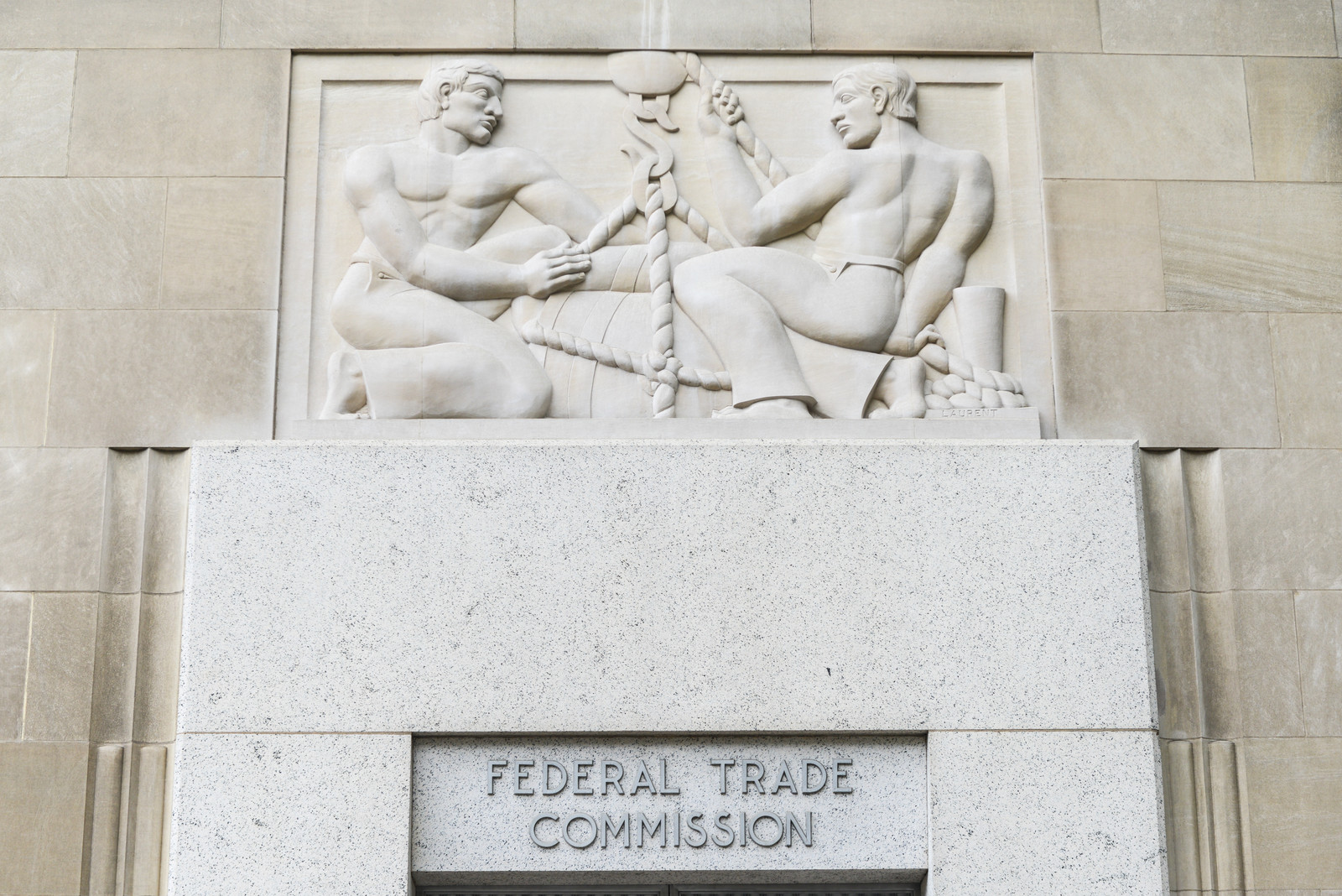 The front door of the Federal Trade Commission building in Washington DC.  With two men above carved out balancing a scale above the door