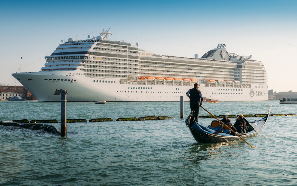 A MSC cruise ship in Venice with a gondola in front of it
