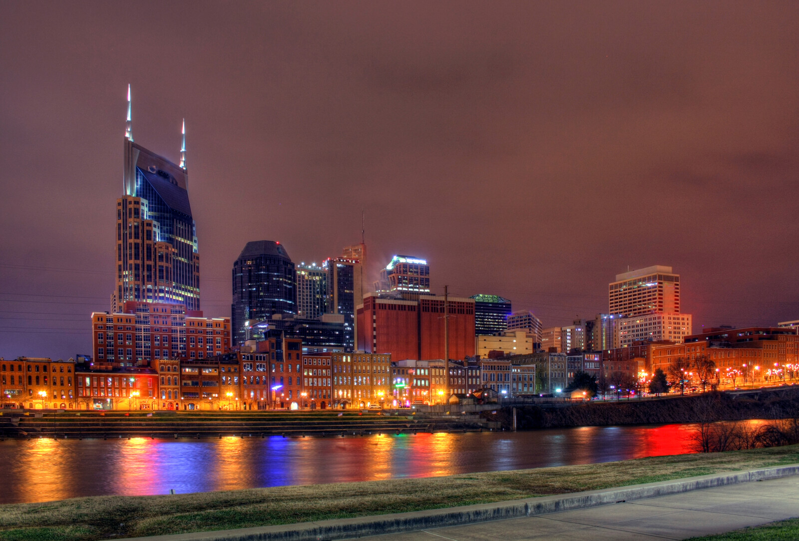 Nashville skyline at night , cloudy gray purple skies in the background with the city lights reflecting off the water