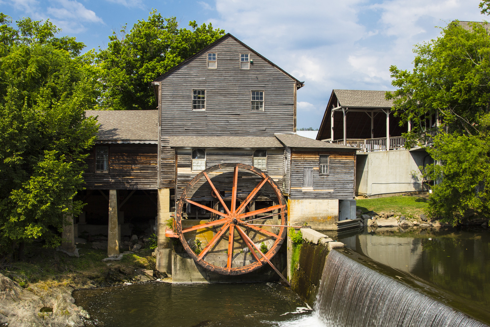 Pigeon Forge Mill with water wheel on the river with trees lining the river