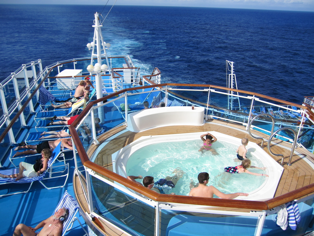 The deck of a Princess cruise ship with people swimming and sunbathing