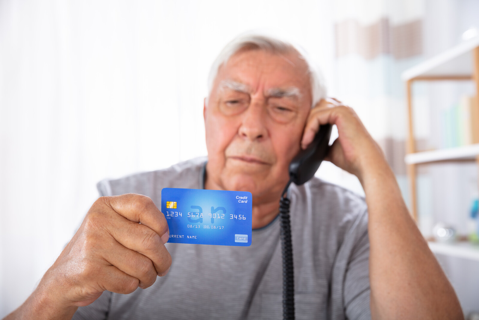 Senior man on the phone reading holding his credit card like he is getting ready to give the information over the phone
