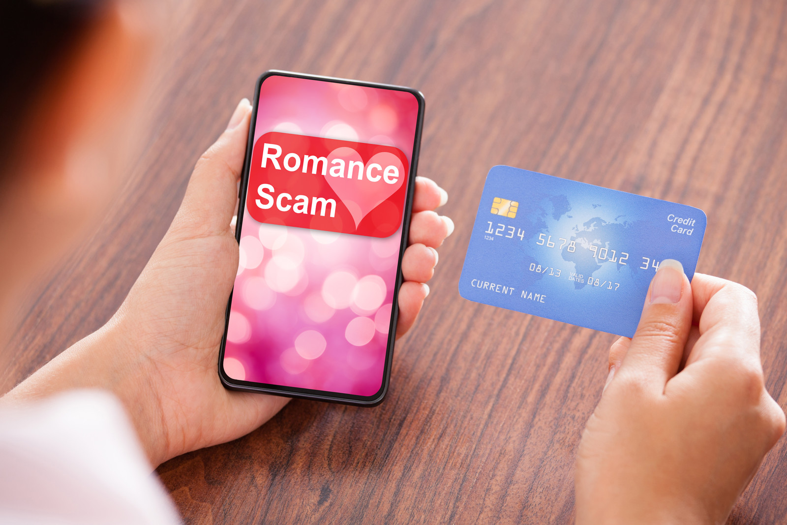 A person blurred out, holding a phone that says Romance Scam in their left hand and in their right hand a credit card
