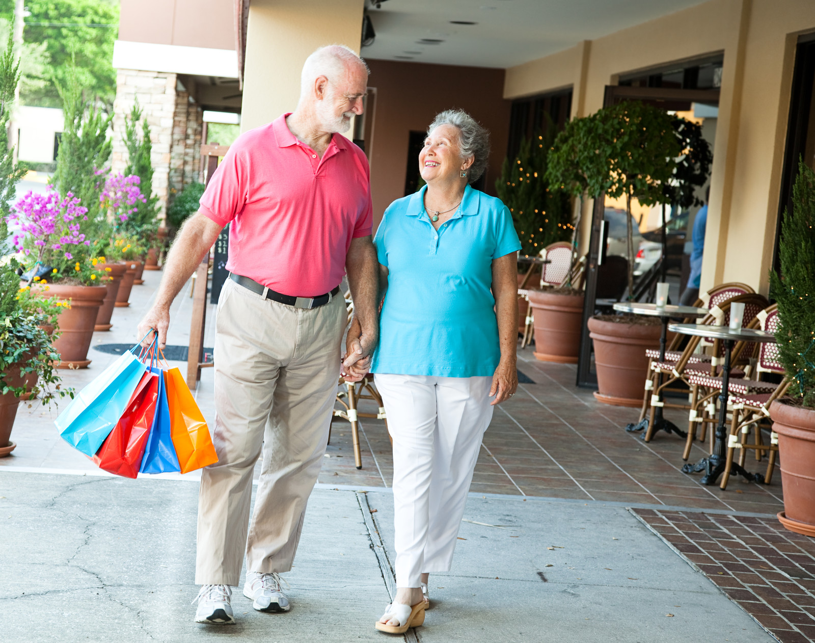Shopping Discounts for Seniors-Senior Couple holding hands smiling at an Outdoor Shopping Mall.  The man is holding four colorful bags and the sidewalk is lined with potted flowers