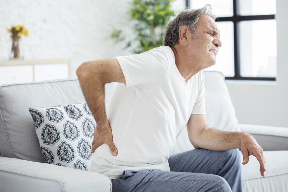 Senior man with back pain sitting on his couch