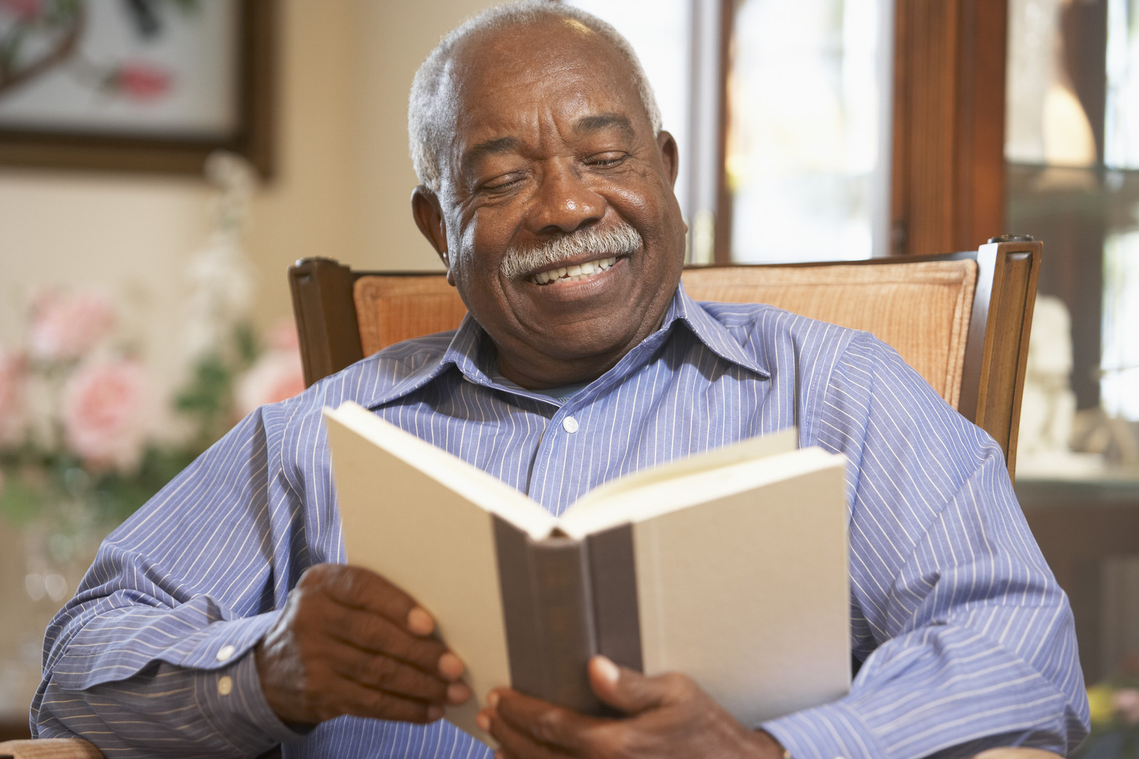 Senior man sitting in a chair with a book smiling and reading
