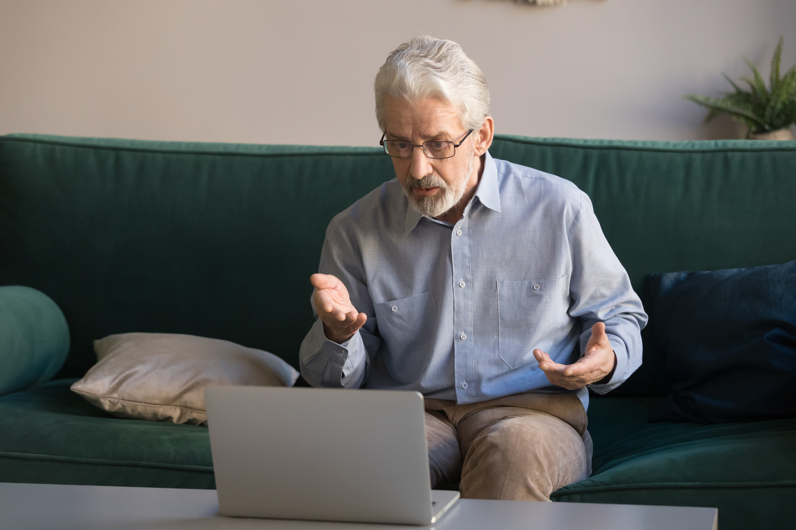 Senior man sitting on a green couch looking down into a laptop explaining something