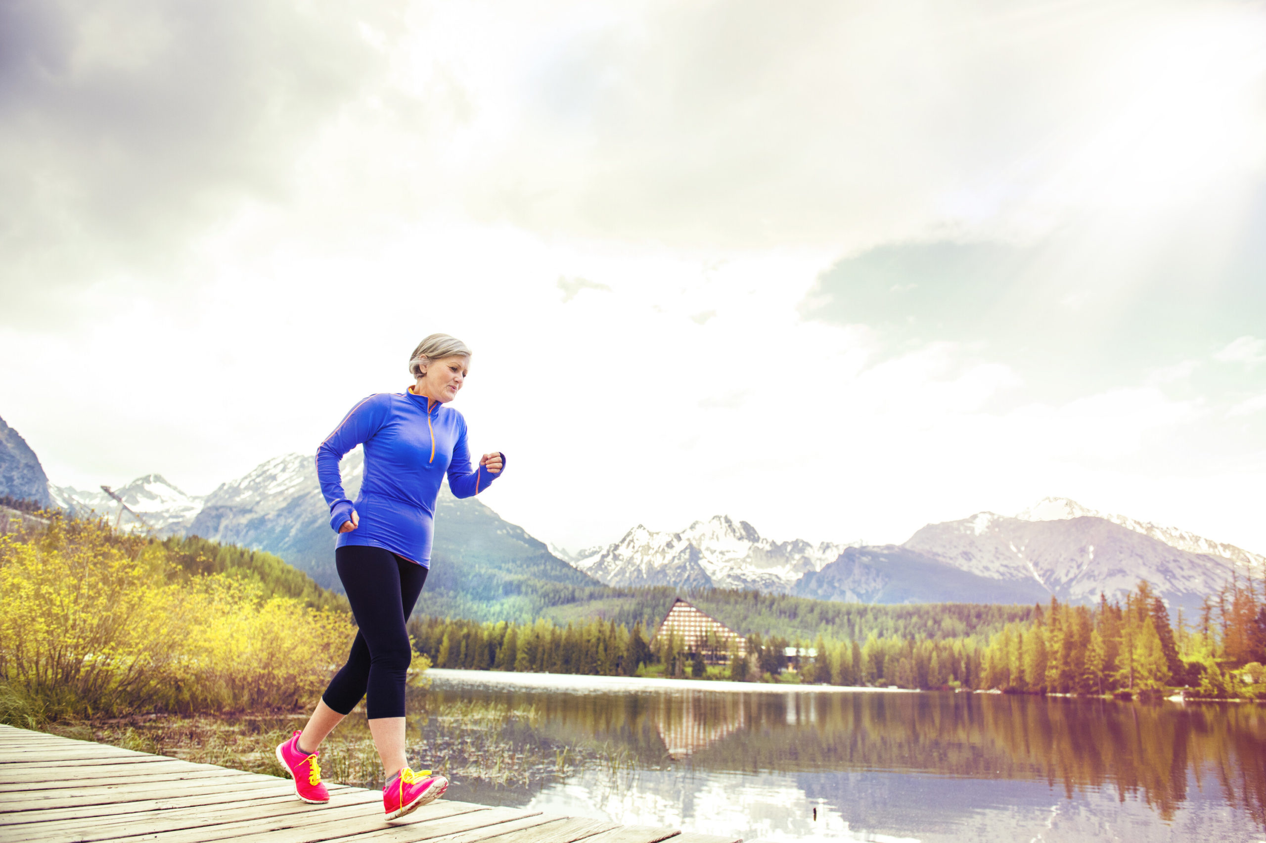 Senior woman jogging on a wooden plank trail with mountains and hills in the background