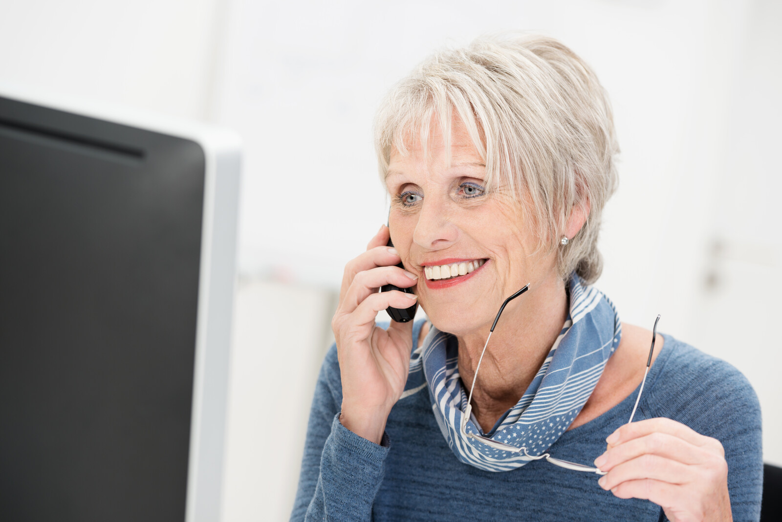 Senior woman smiling while on the phone looking at a computer screen and holding her glasses.