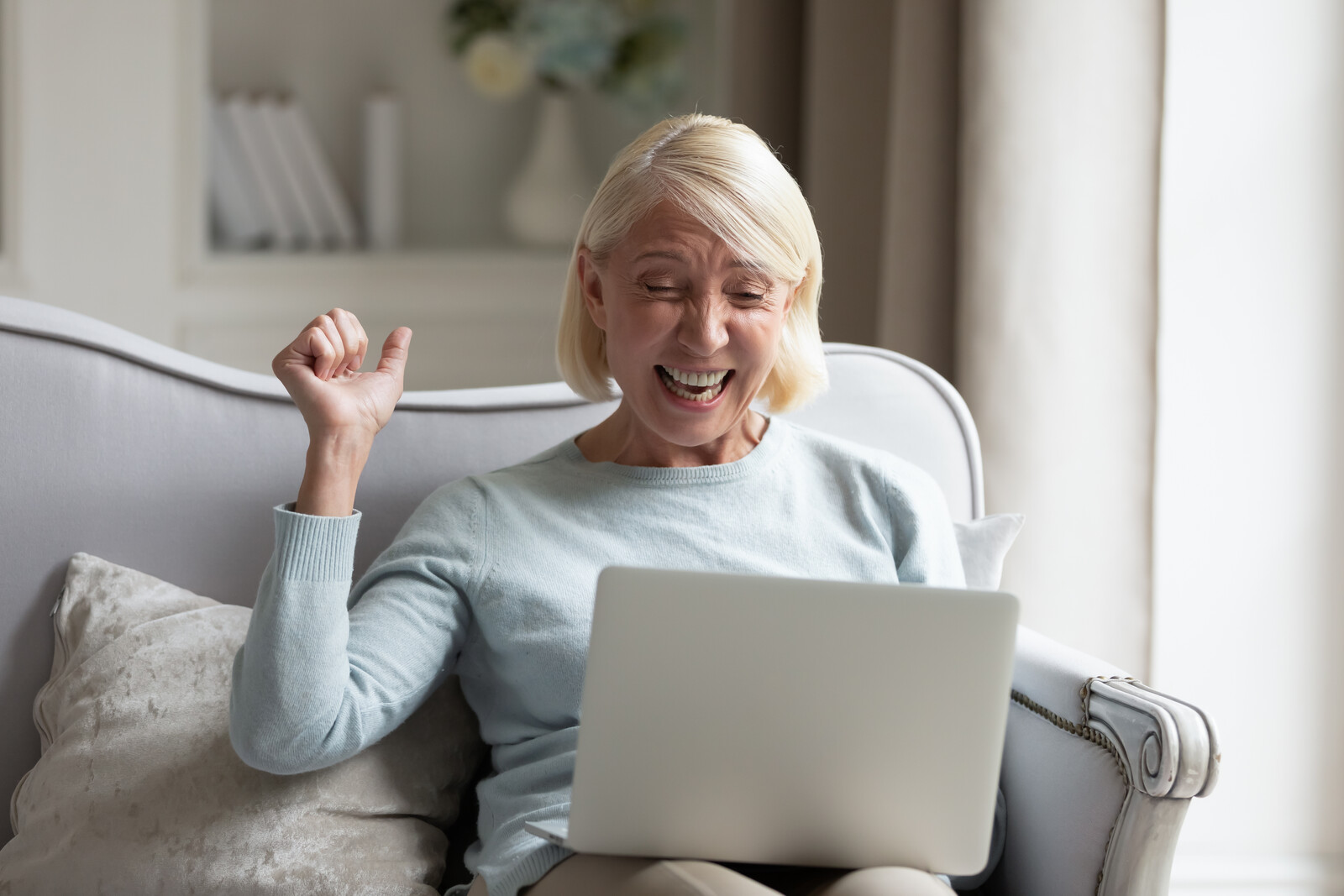 Senior woman on her couch with a lap top on her lap smiling doing fist pump in the air showing her happiness as if she won a gift card