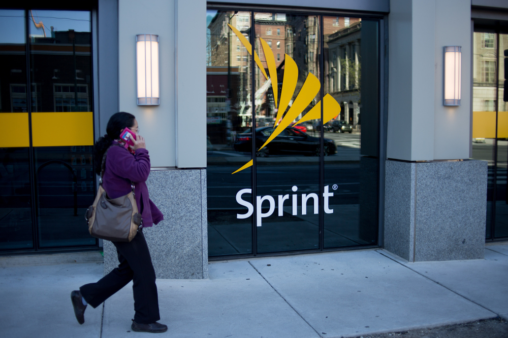 A woman walking past a Sprint store