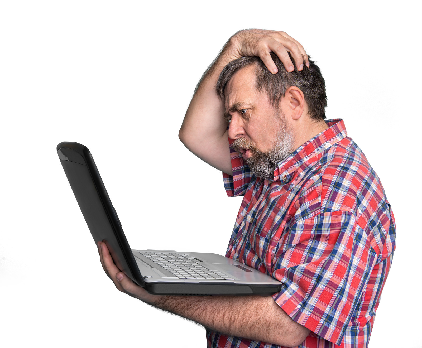 Older man with his hand on his head and a look of confusion on his face as he looks at the screen of a laptop computer in his other hand