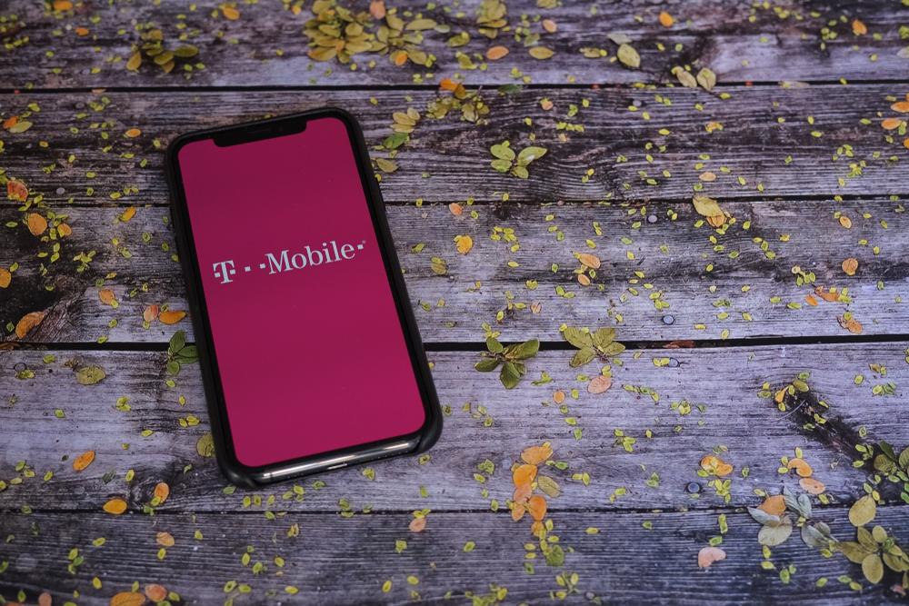 A cellphone on a wooden table with the T-Mobile app