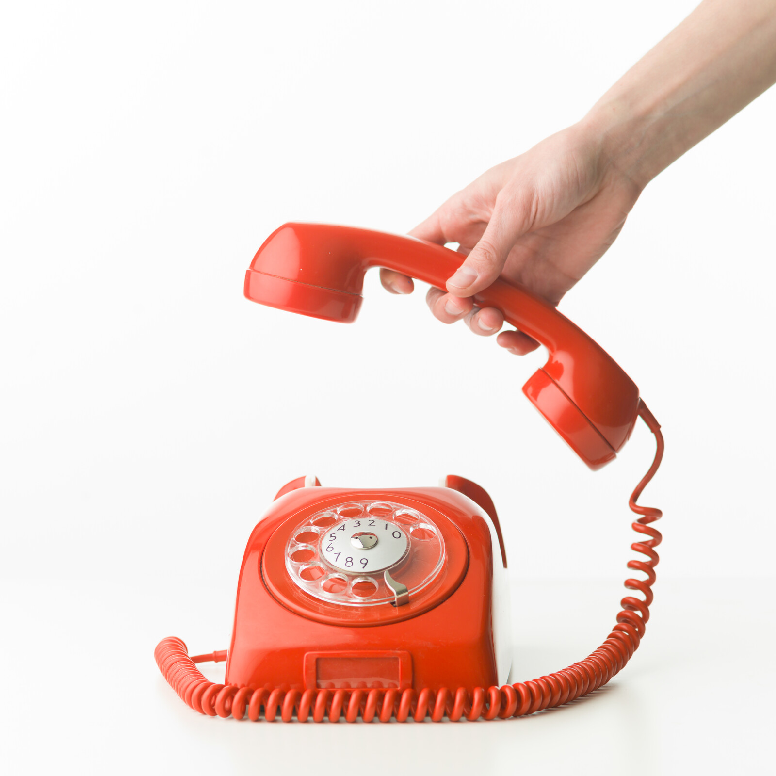 Orange rotary phone with someone's hand hanging up the receiver