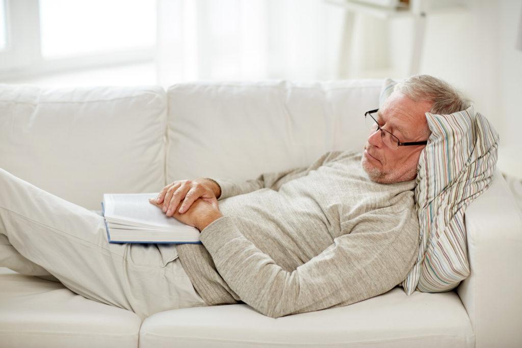 A senior man sleeps on the sofa.