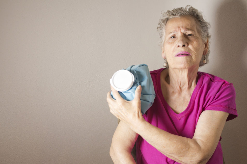 A senior woman with a cold pack on her shoulder.
