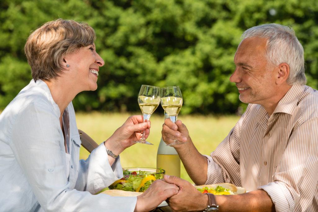 A senior couple eating a meal outside.