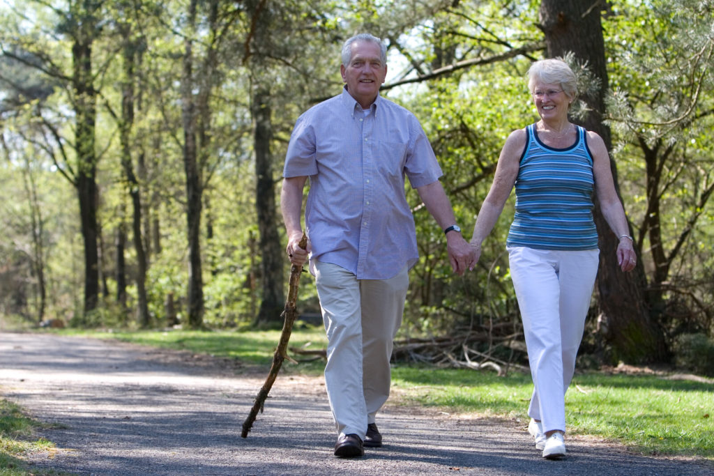A senior couple walking at the park.