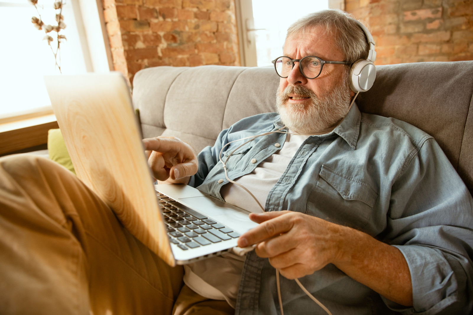 Senior man in a denim shirt sitting on a couch pointing at his laptop with headphones on
