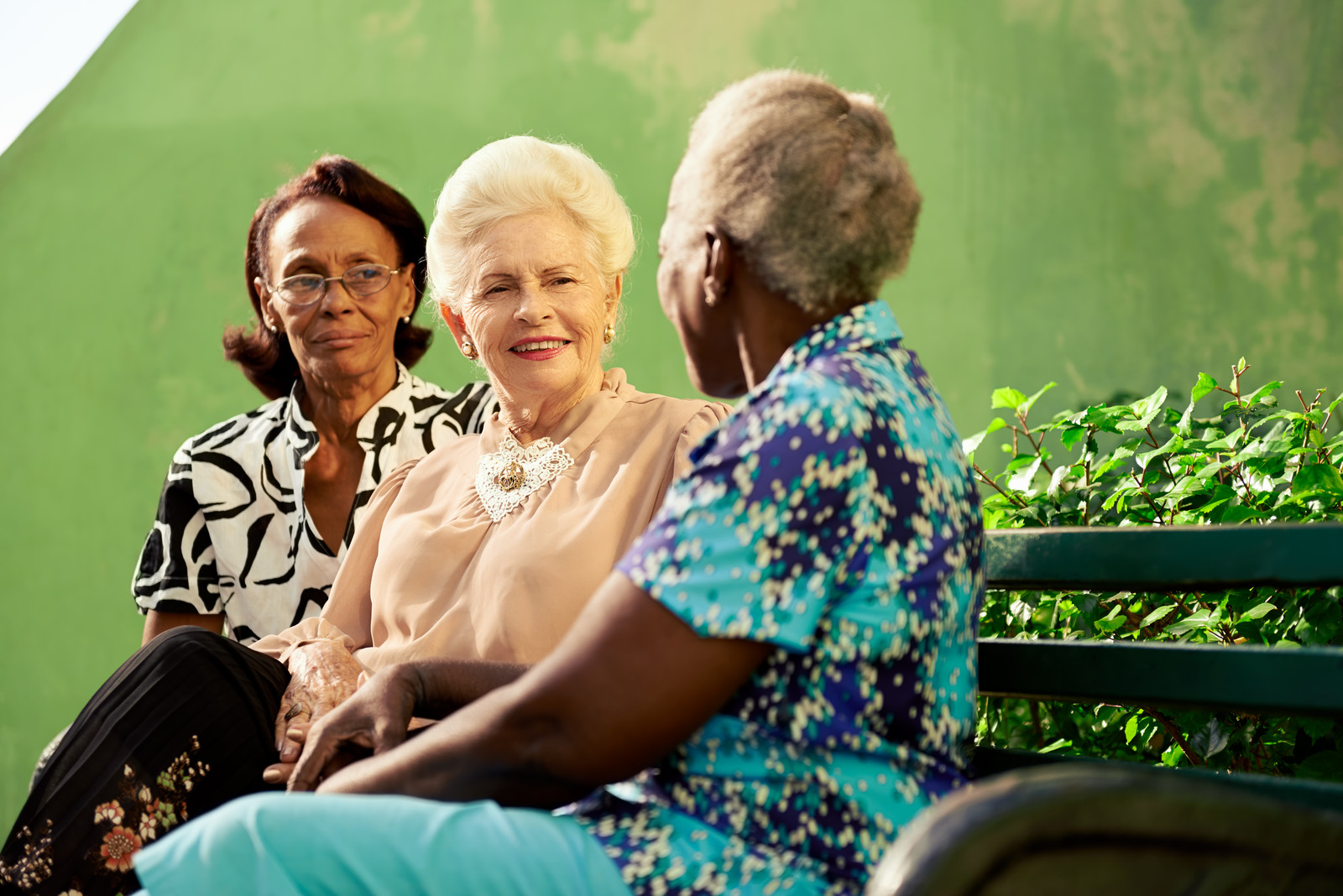 Three senior women on a park bench, green background and shrub behind the bench.  The three women appear to be in conversation