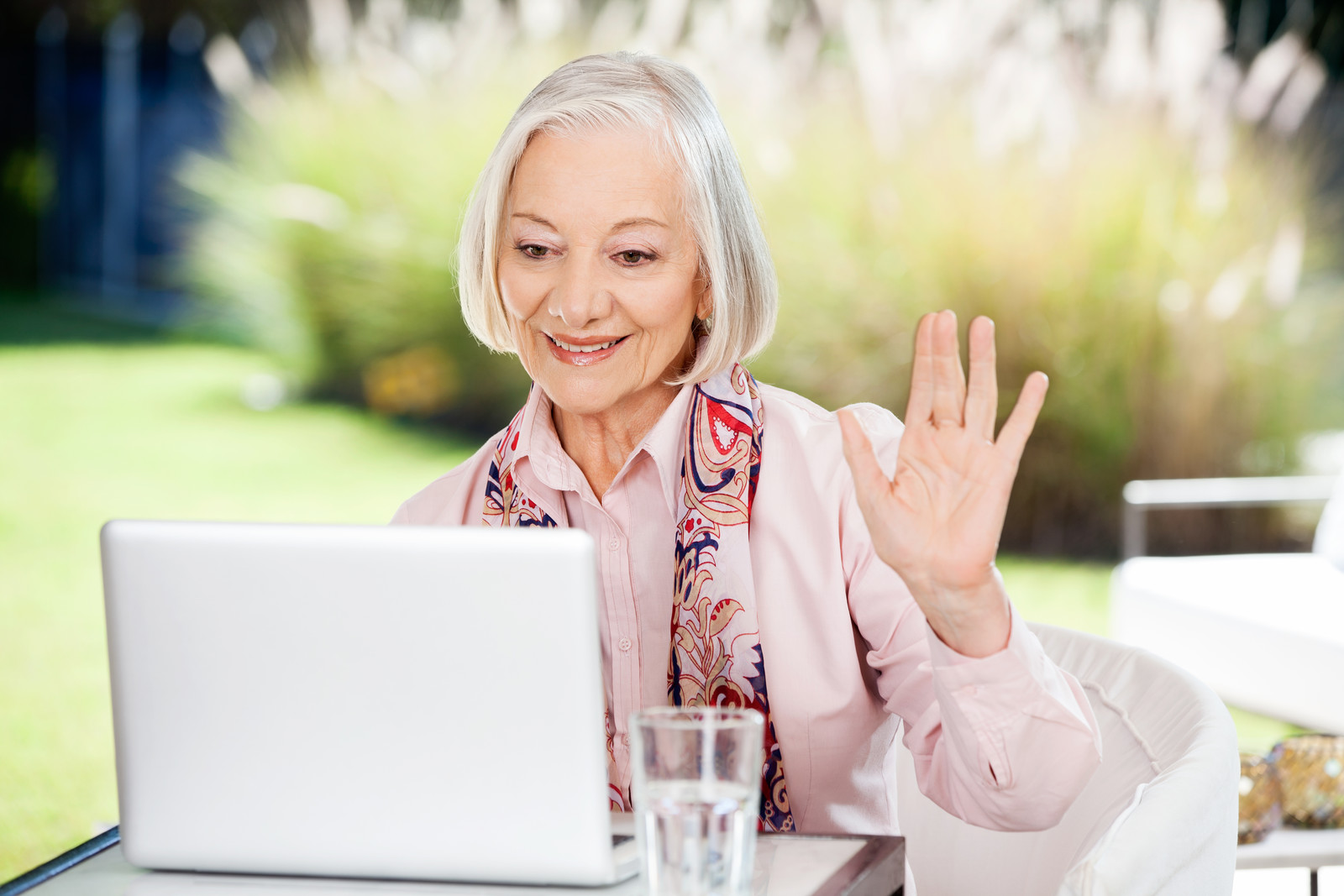 A senior woman waving to someone on the computer sitting outside on a sunny day.  A glass is sitting on the table and she's smiling.  blurred out trees in the background.