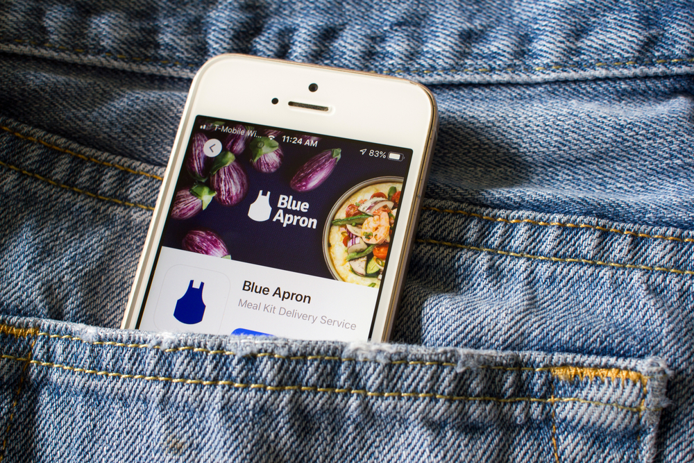 A cellphone in someone's jean pocket with the Blue Apron cellphone app on it