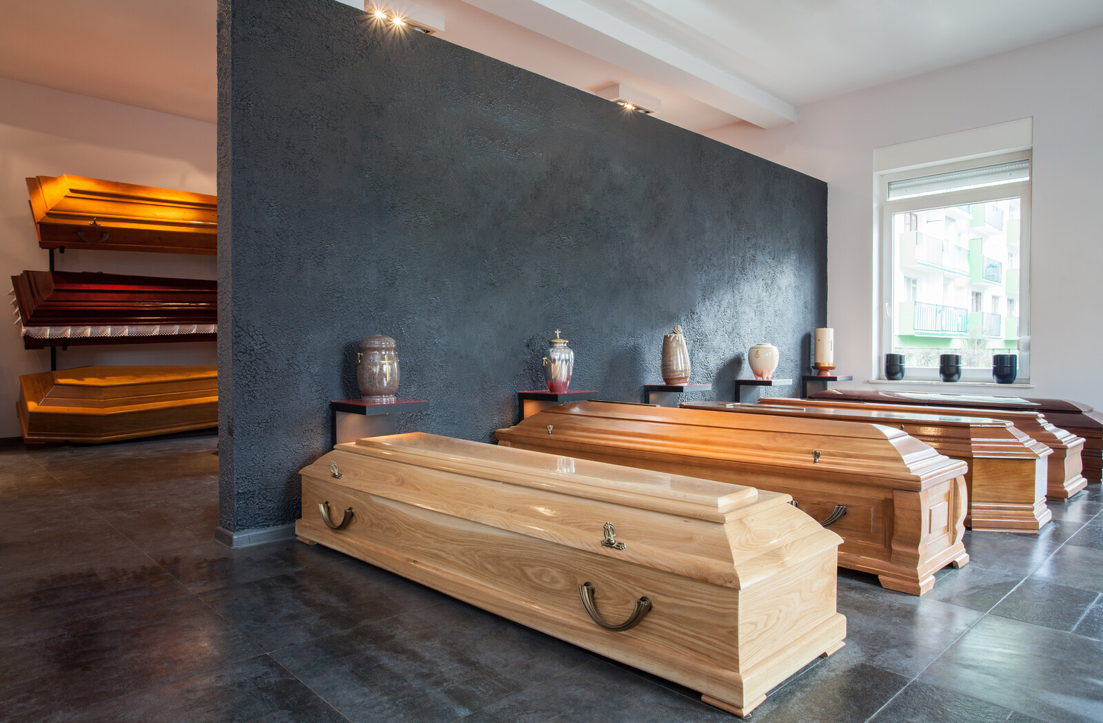 Funeral home showroom with caskets and urns