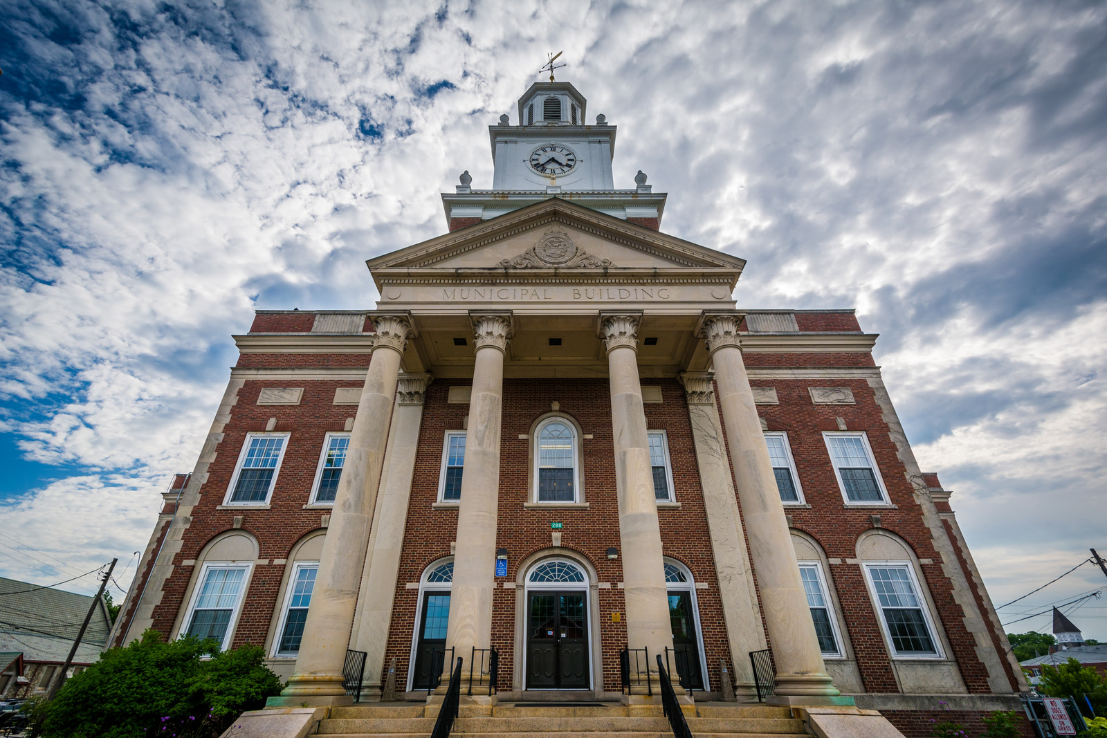 City Hall , tall brick building with four large pillars and a clock tower, in Dover New Hampshire