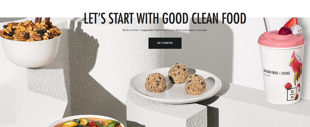 Daily Harvest website screenshot showing some plates and containers of food on white blocks against a white background