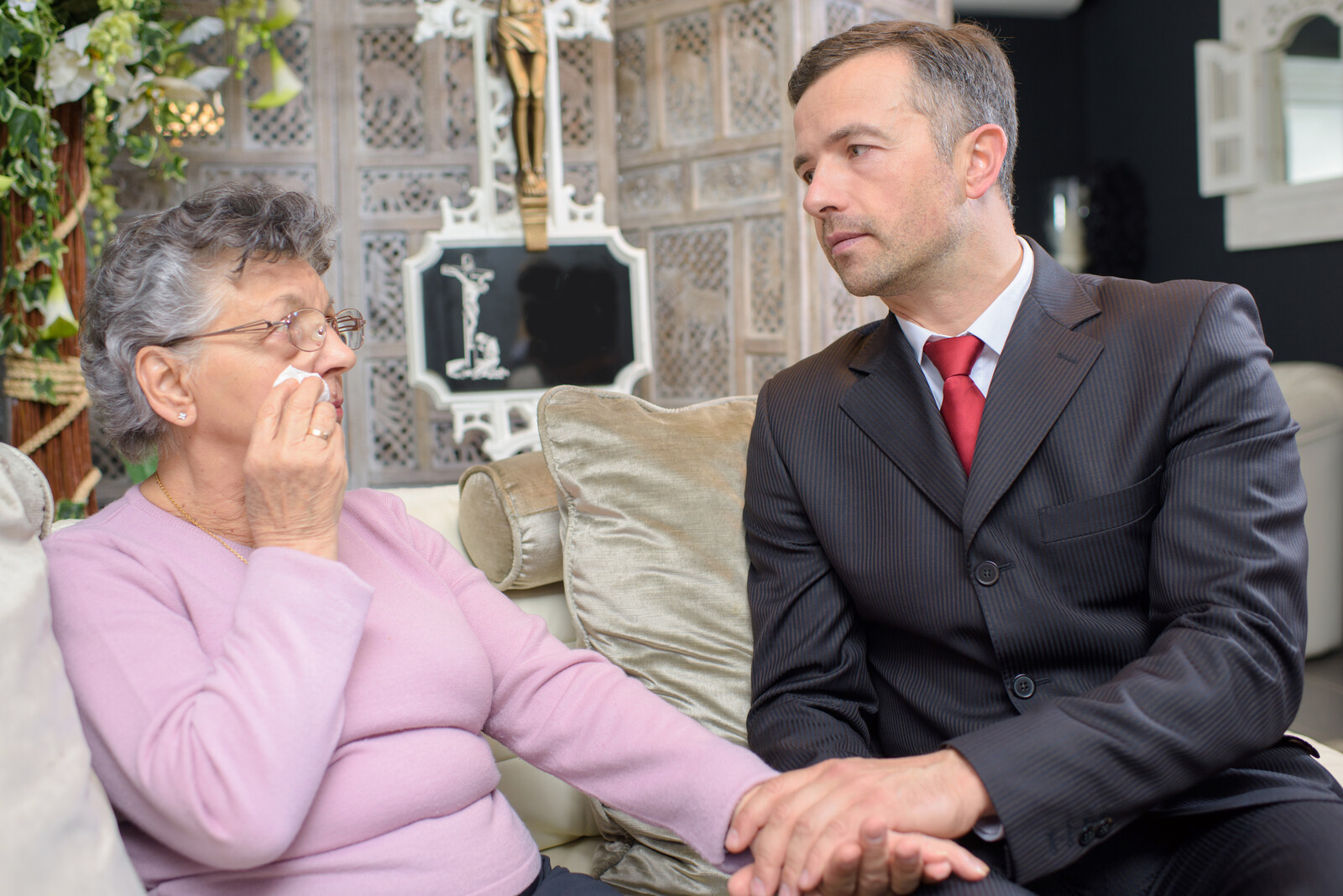 Funeral director sitting on a couch at funeral home with senior woman who is crying, holding her hand