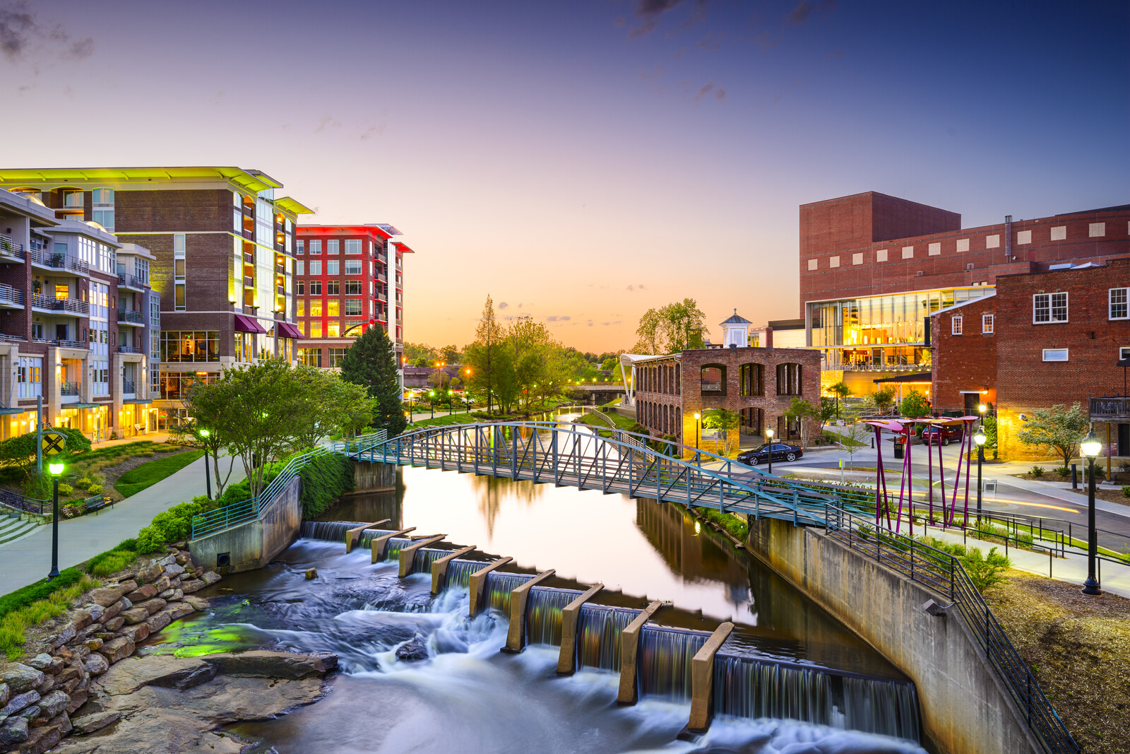 Greenville city-scape with a footbridge over the river and waterfall at sunset