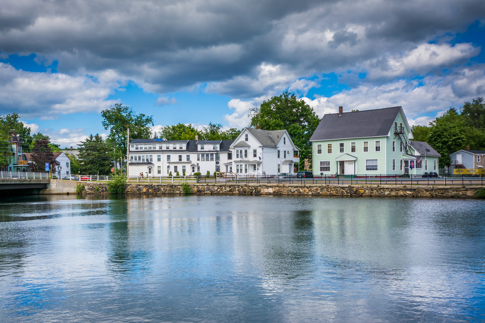 Houses along the Winnipesaukee River, in Laconia, New Hampshire.  Blue skies reflected on the water and on the left of the photo a small bridge