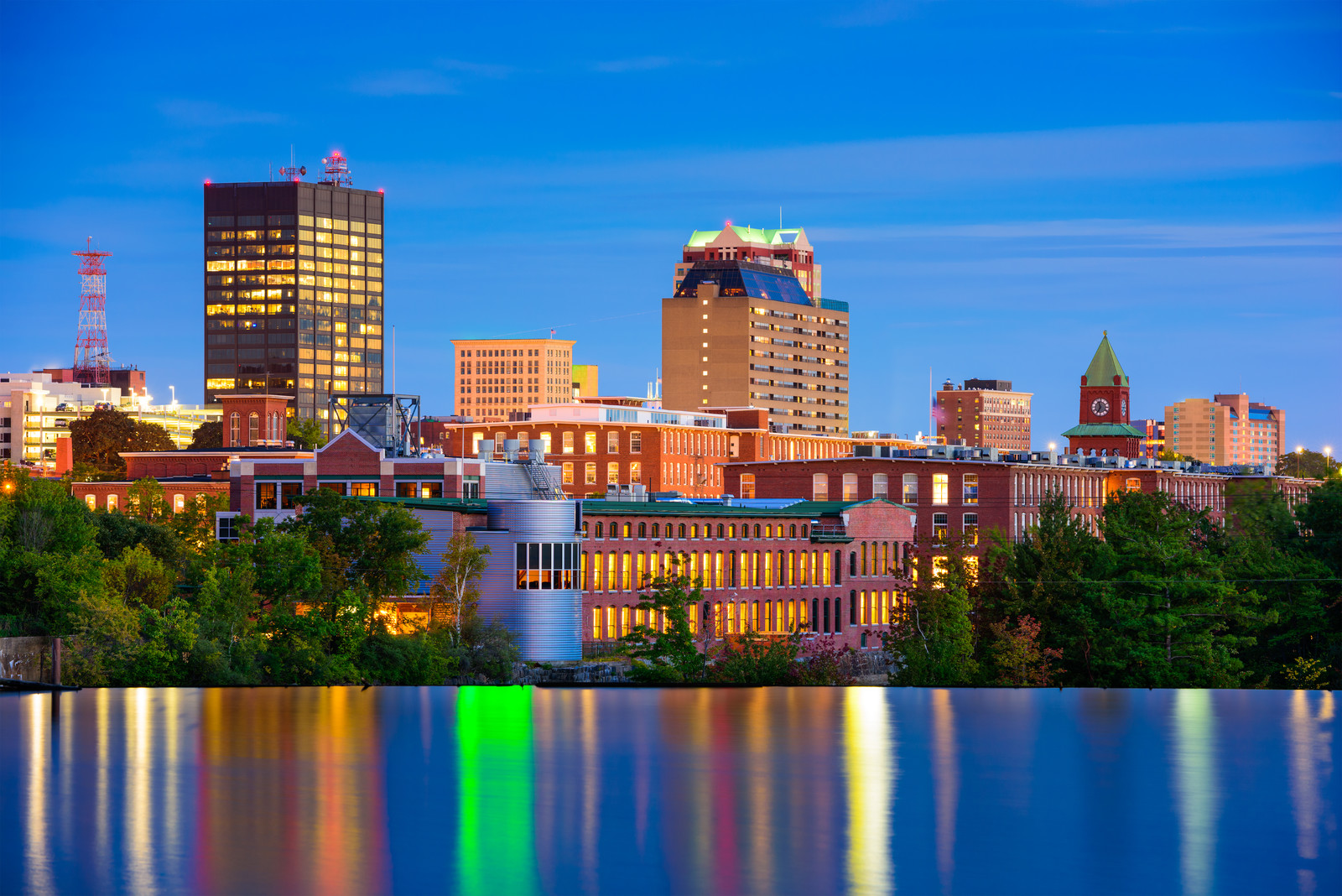 Manchester, New Hampshire Skyline on the Merrimack River in the evening with the lights reflecting off the still water