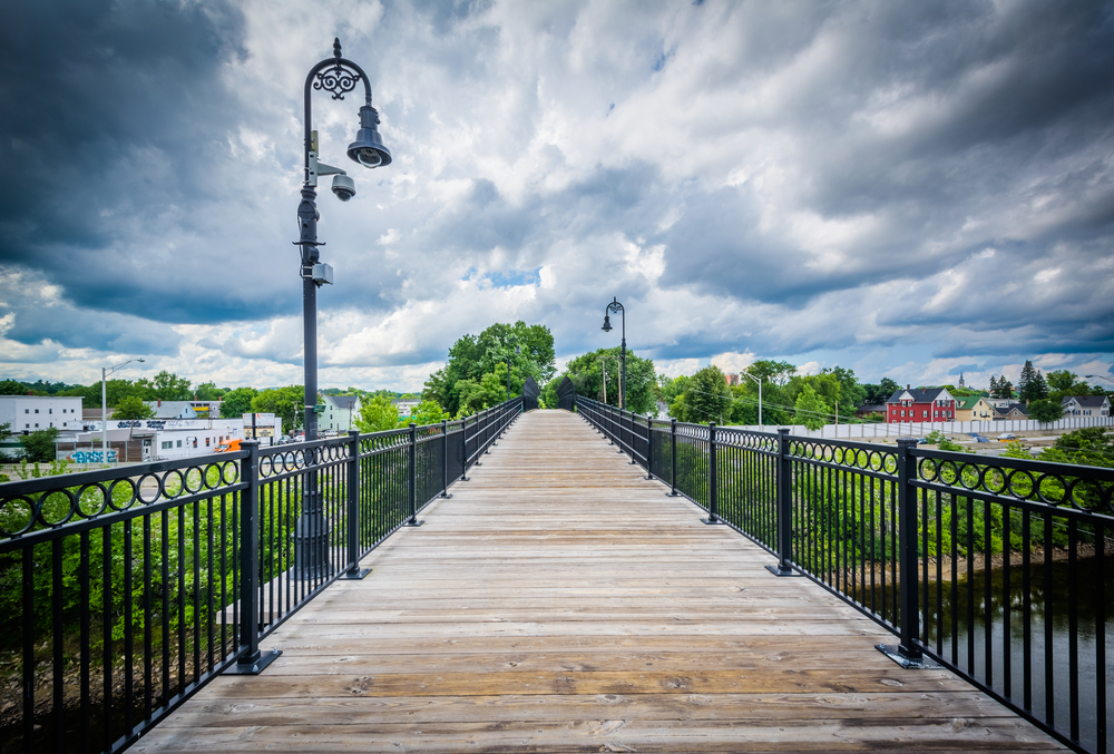 Pedestrian bridge running over the Merrimack river in Manchester New Hampshire, showing a metal railing, wooden footpath, lamps and clouds