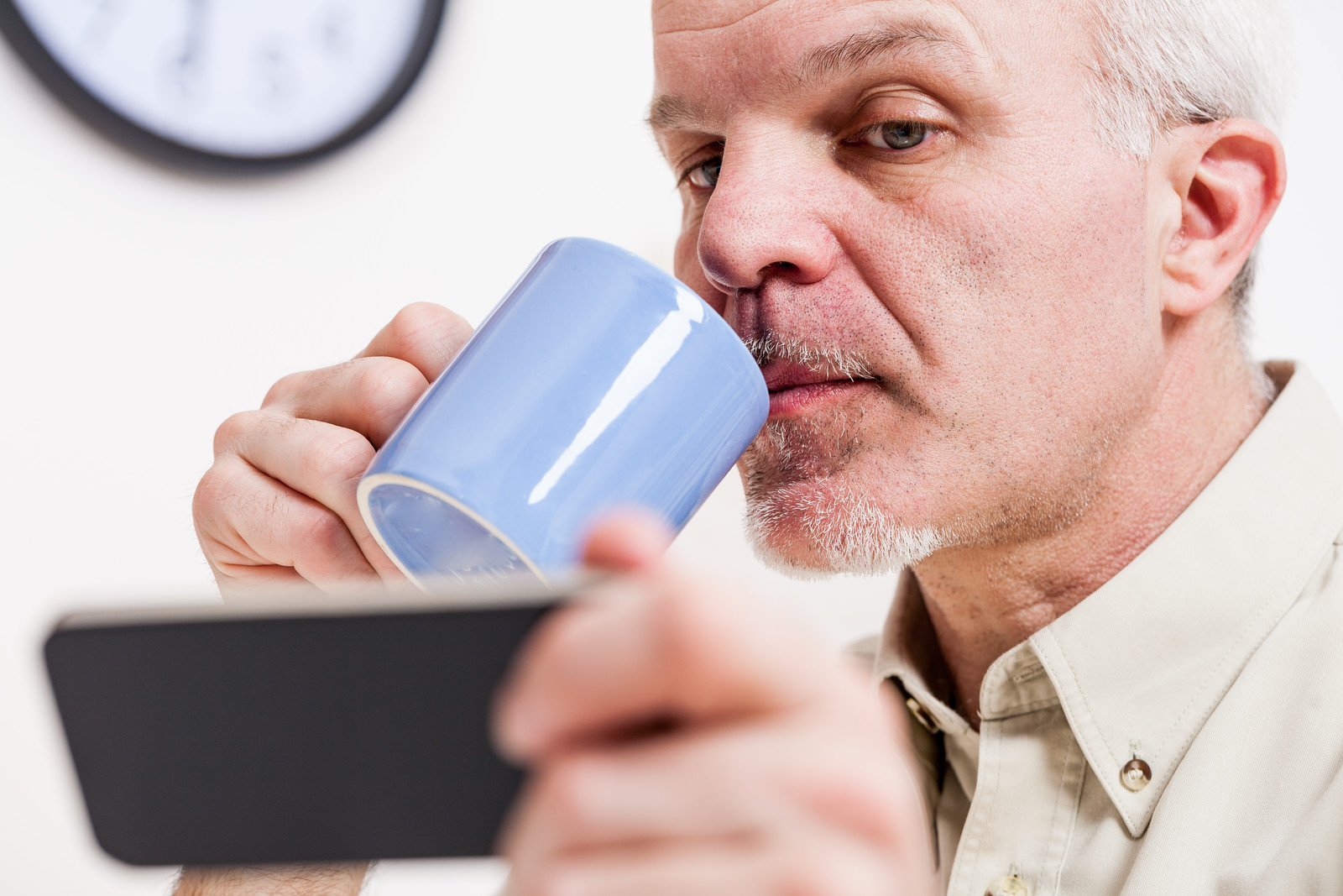 Senior man looking at his phone with a suspicious look on his face drinking a cup of coffee