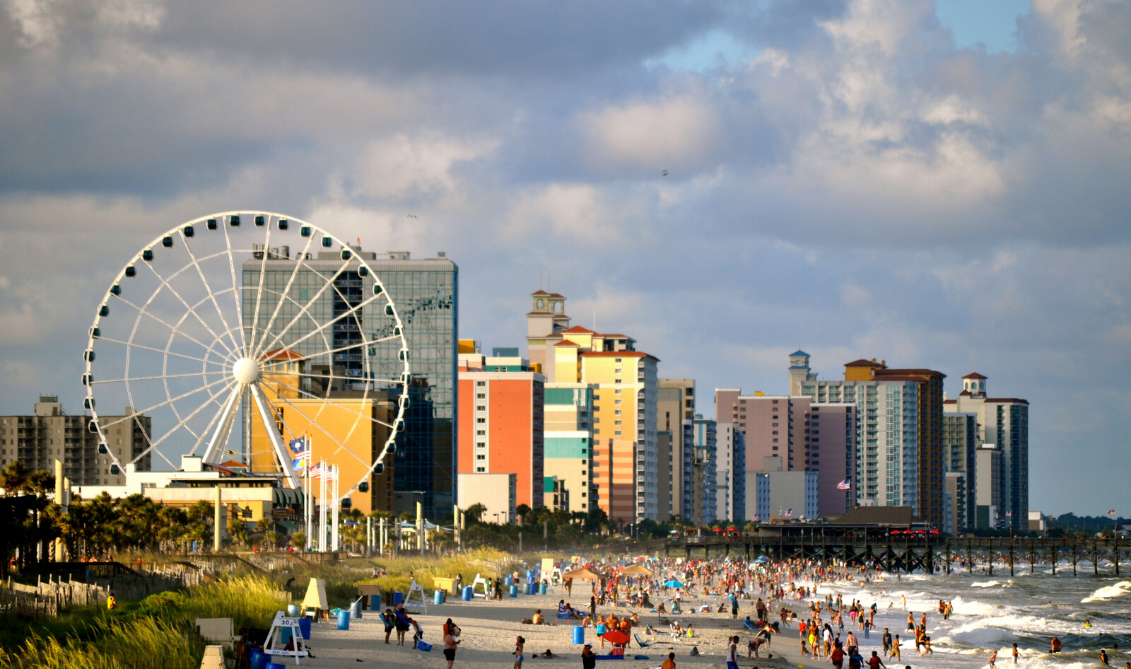 Myrtle beach coastline with skyline and Ferris wheel in the background.  And lots of people dotting the sandy beach