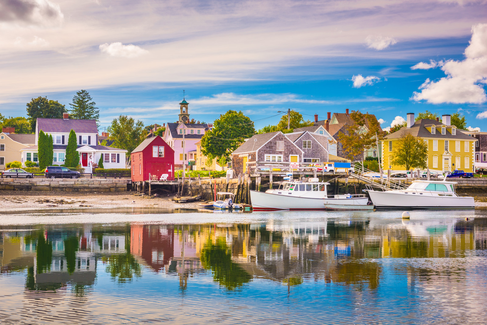 Colorful houses lining the Piscataqua River in Portsmouth, New Hampshire,  With two white boats docked on the shore