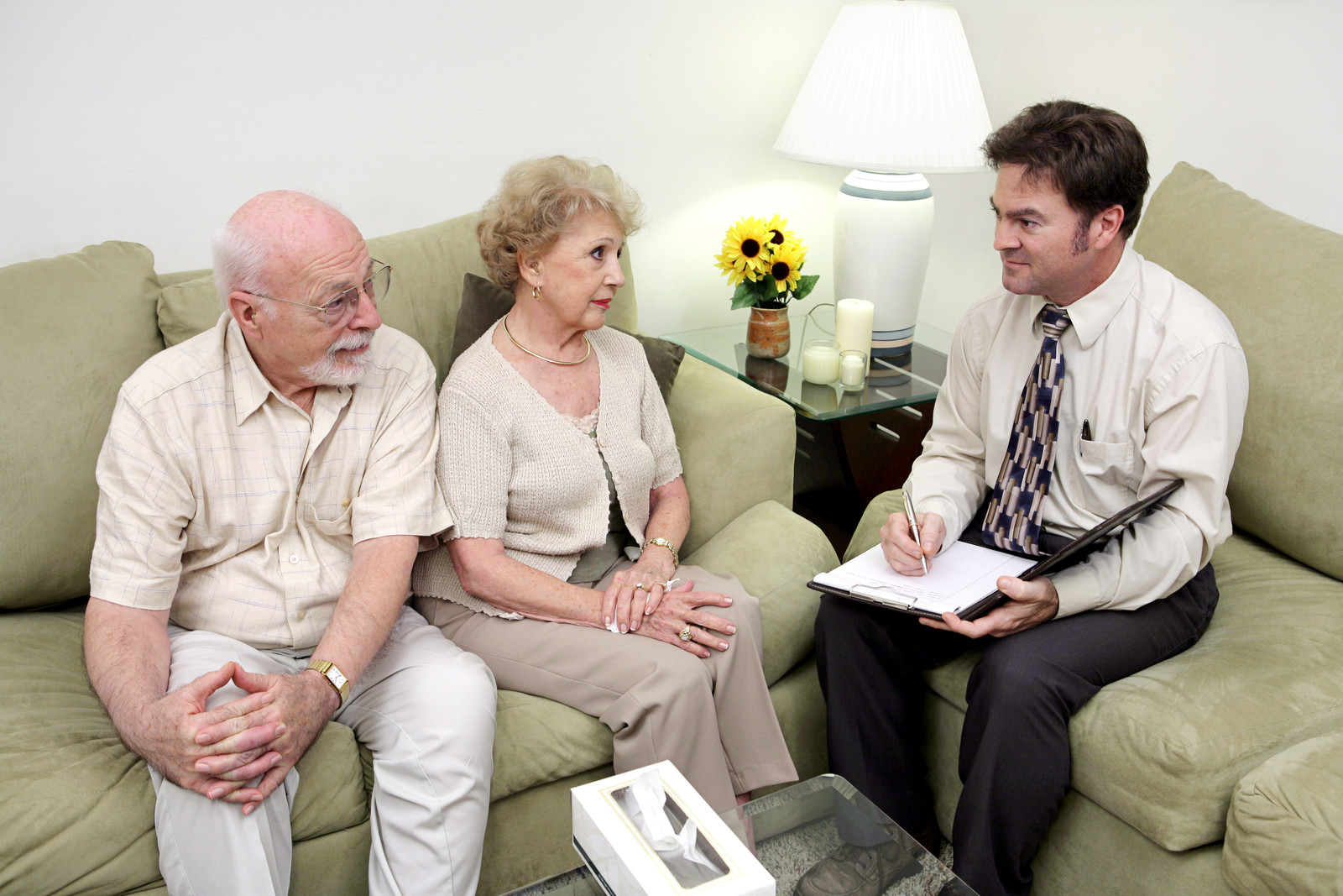 Seniors couple sitting on a couch talking with a man who is sitting kitty corner on another couch, in a button down and tie holding a pad of paper