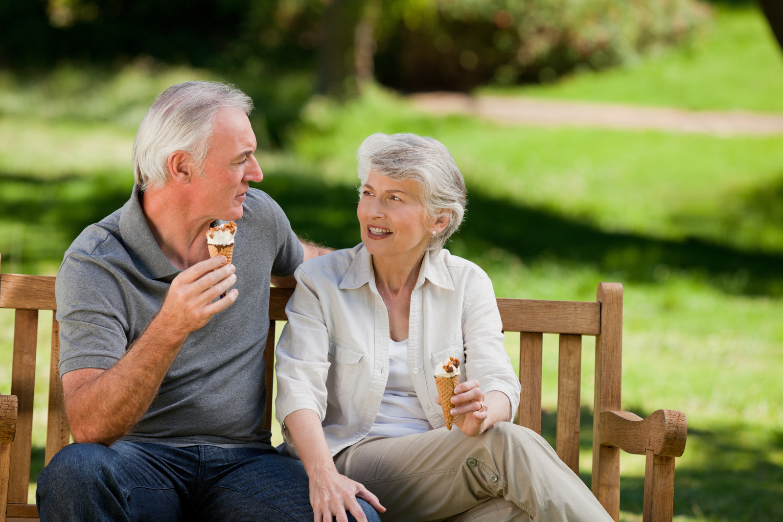 Senior online dating scams - Senior couple sitting on a wooden park bench eating ice cream cones