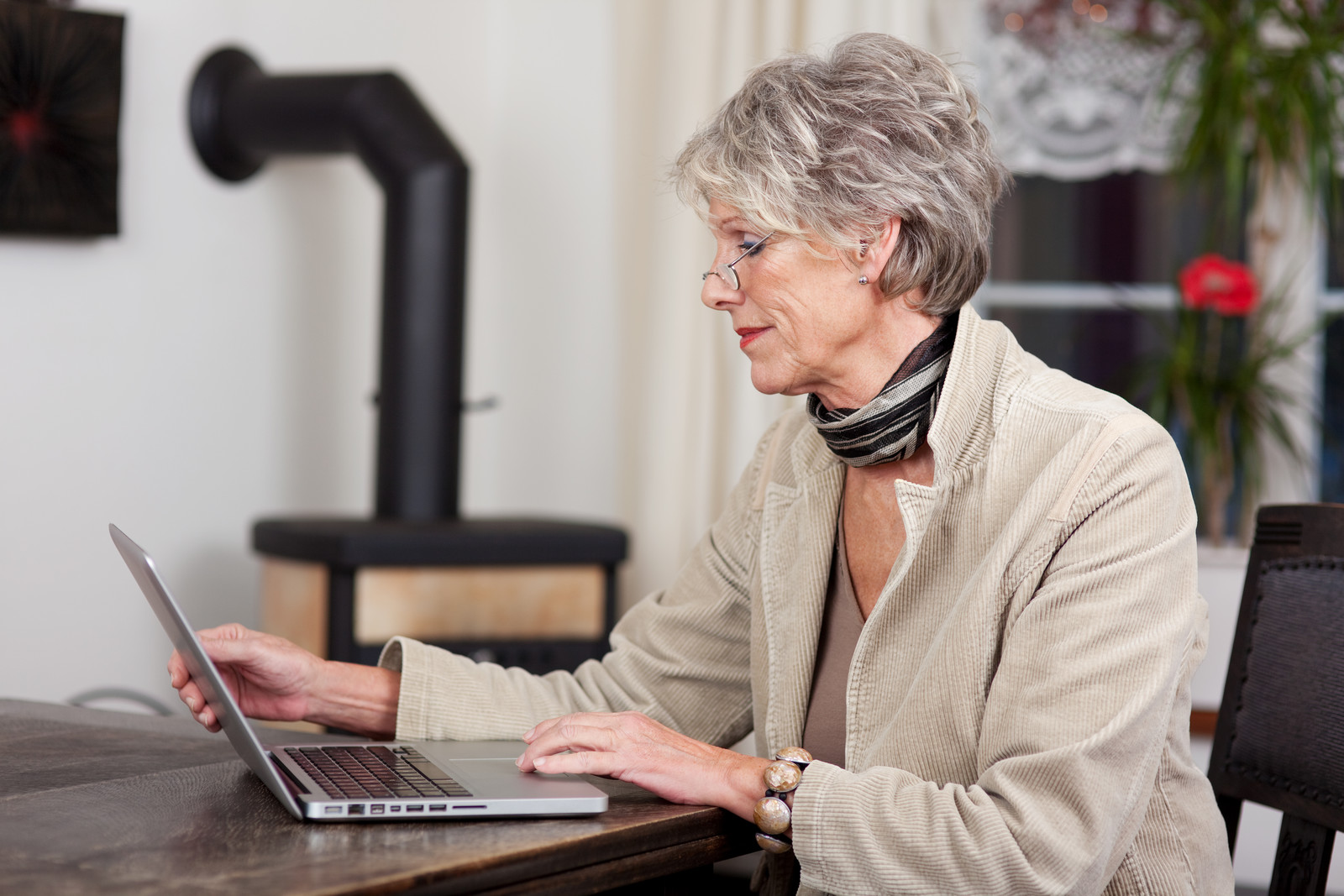 Senior woman researching online using her laptop at home