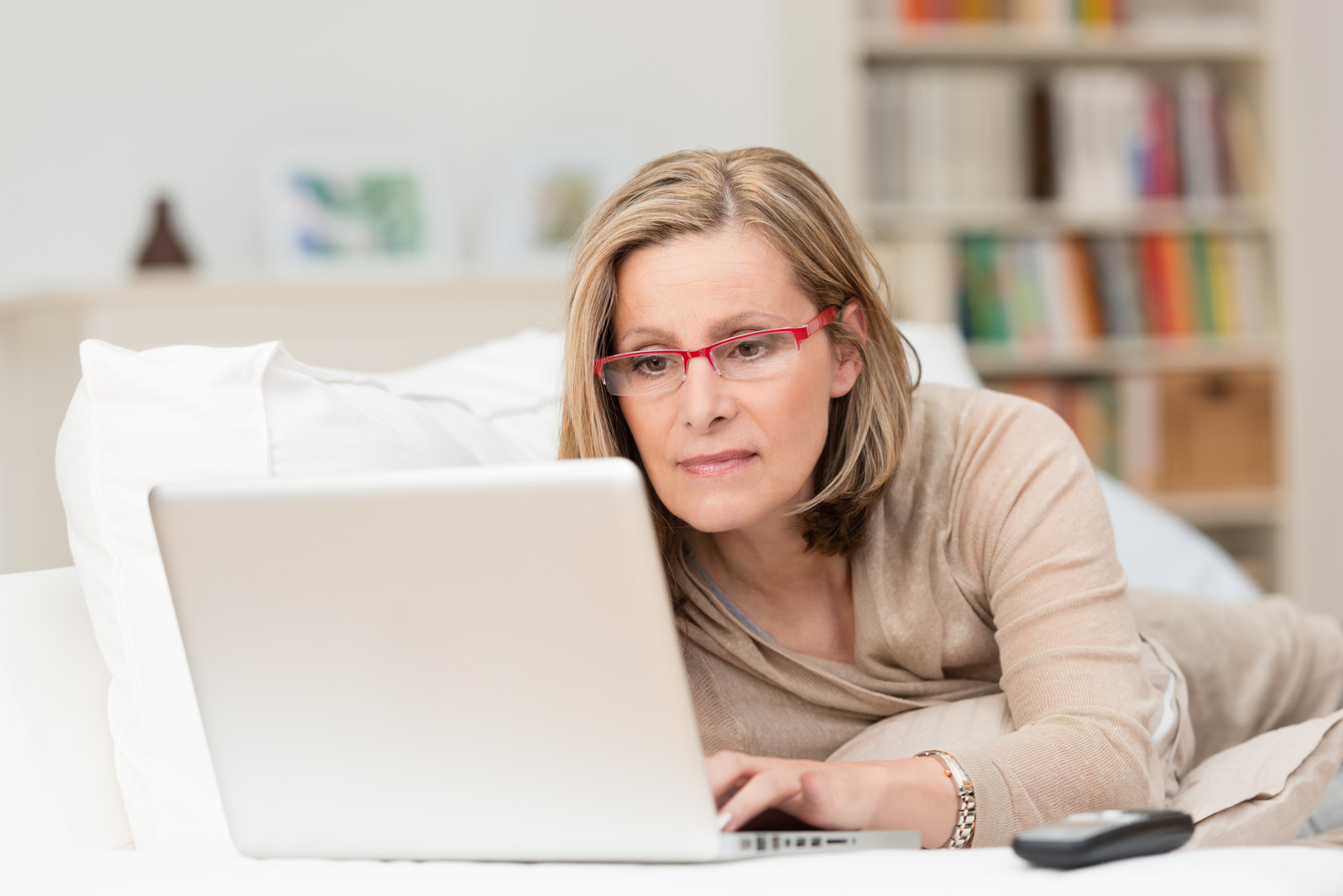 Senior woman wearing reading glasses laying on couch working on her laptop