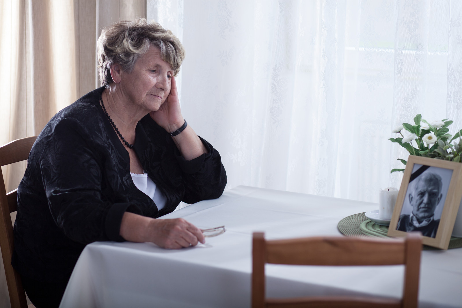 Senior woman sitting at her kitchen table looking at dead husband's picture  white curtains in the background and white tablecloth