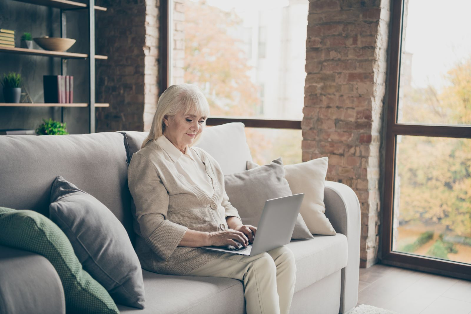 Senior woman sitting on the couch smiling as she types on her laptop