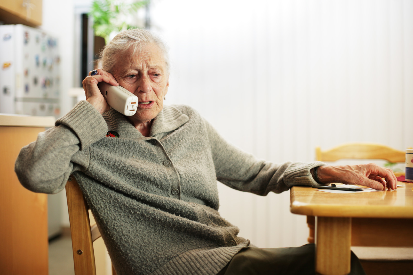 Senior woman talking on the phone while sitting at a table with a concerned look on her face