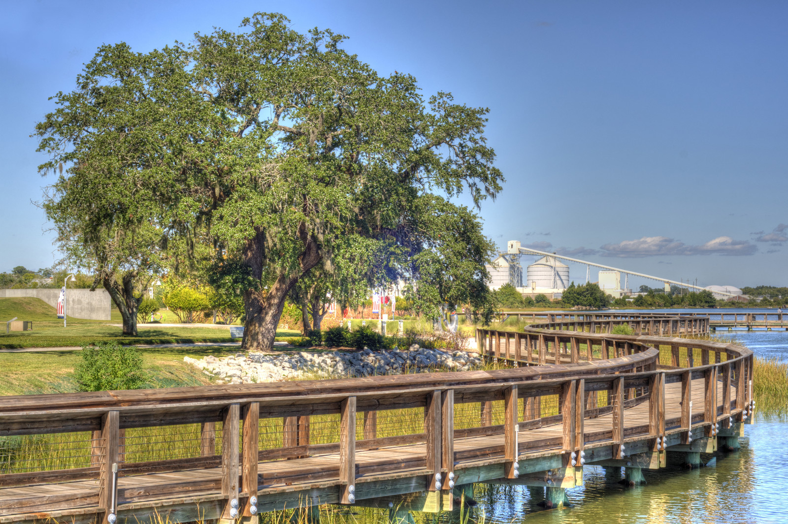 Southport NC boardwalk along the water with green trees in the park and the industrial district in the background
